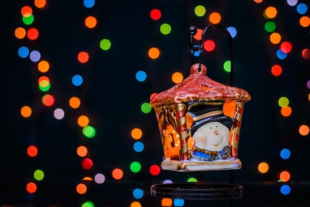 Neujahrslaternenkerzenhalter auf dem hintergrund des bunten bokehs von der weihnachtsfeiertagsbeleuchtung