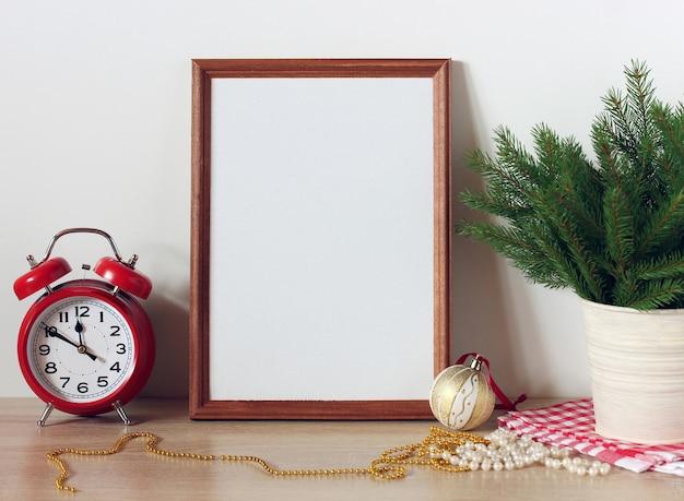 Neujahrsmodell mit einem leeren rahmen, einem wecker und zweigen des weihnachtsbaums in einem eimer auf dem tisch eine festliche kulisse ein platz für text oder zeichnung