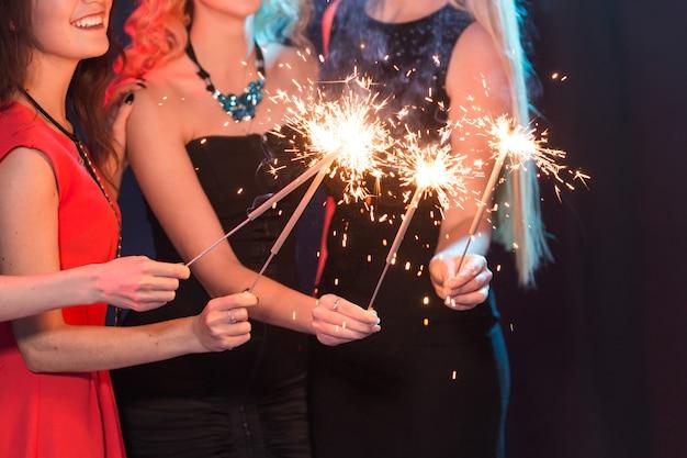 Neujahrsparty, feier und feiertagskonzept - gruppe von freunden, die spaß mit wunderkerzen haben.