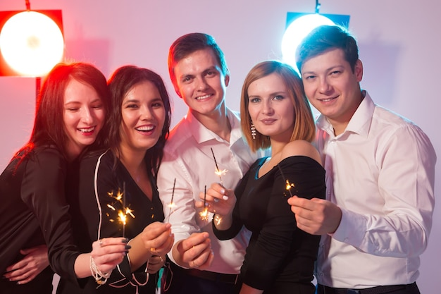 Neujahrsparty, feier und feiertagskonzept - gruppe von freunden, die spaß mit wunderkerzen haben
