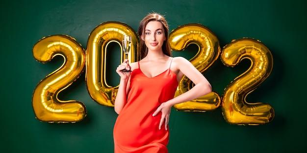 Neujahrsparty luftballons konfetti grüne hintergrundfrau mit champagner feiern