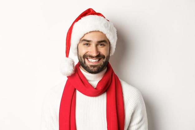 Neujahrsparty und winterferienkonzept. nahaufnahme des fröhlichen kaukasischen mannes, der weihnachten in sankt-hut feiert und glücklich lächelt, weißer hintergrund.