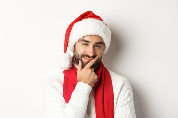 Neujahrsparty und winterferienkonzept. nahaufnahme eines bärtigen mannes mit weihnachtsmütze, der nachdenklich in die kamera schaut, nachdenkt oder eine entscheidung trifft, weihnachtsgeschenk wählt, weißer hintergrund