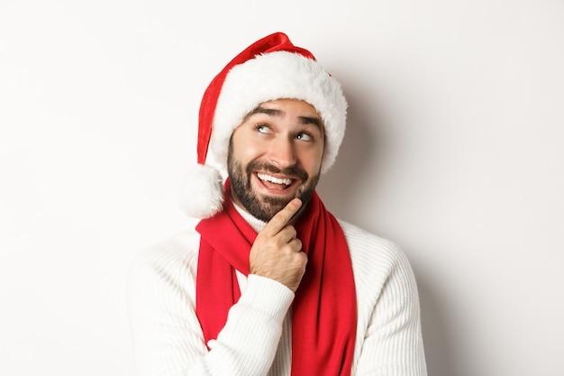 Neujahrsparty und winterferienkonzept. nahaufnahme eines gutaussehenden bärtigen mannes, der nachdenklich aussieht und weihnachtsgeschenkliste in weihnachtsmütze plant, weißer hintergrund