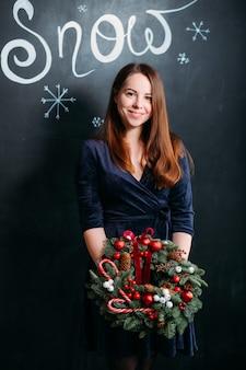 Neujahrspartygeschenk. frau im blauen kleid, das mit handgemachtem weihnachtskranz über dunkler wand mit schneeschrift steht.