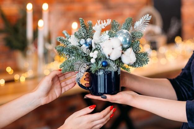 Neujahrspartygeschenk. nahaufnahme der tannenbaumanordnung mit weißem kunstschnee, hirsch und baumwollpflanze im becher.
