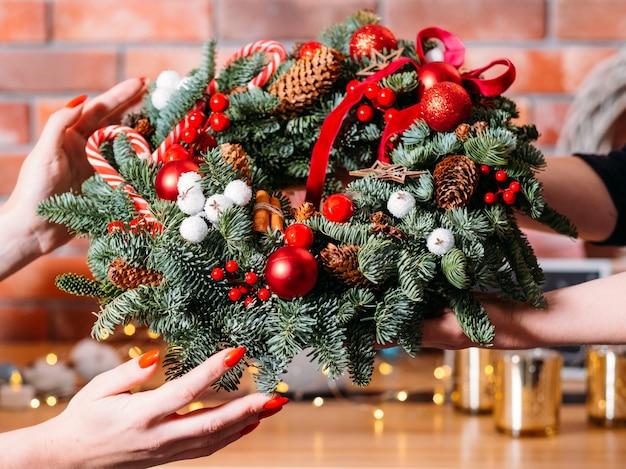 Neujahrspartygeschenk. nahaufnahme des handgemachten weihnachtskranzes verziert mit zuckerstangen, tannenzapfen und roten bändern.