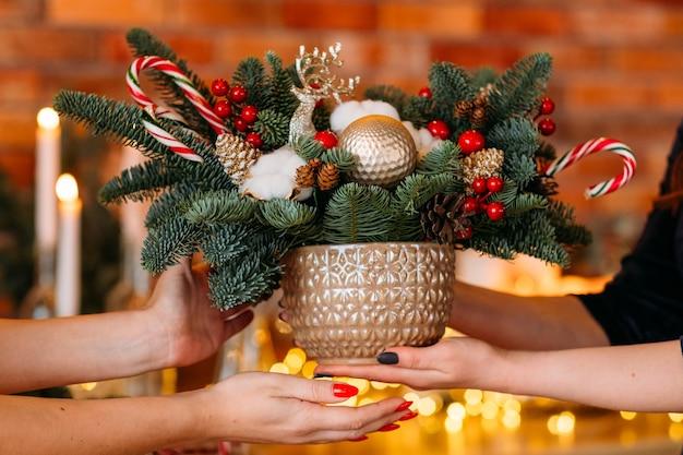 Neujahrspartygeschenk. nahaufnahme des topfes mit tannenbaum, zuckerstangen, hirsch, weihnachtskugelanordnung.