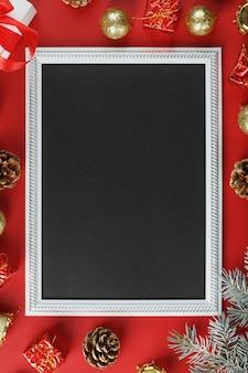 Neujahrsrahmen mit neujahrsspielzeug, tannenzweigen und geschenken in einer umgebung auf einem roten hintergrund. grußkarte mit weihnachten, neujahr mit freiem platz für begrüßungstexte.