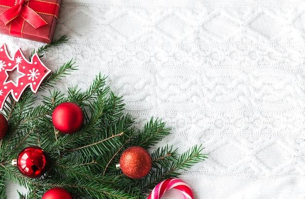 Neujahrsrahmenmodell. tannenzapfen, tannenzweige und weihnachtskugeln auf weiß gestricktem hintergrund