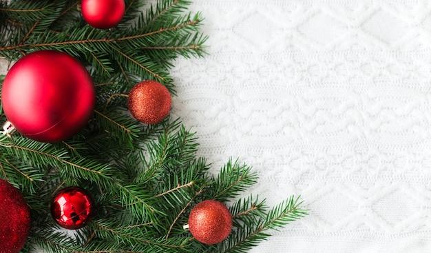 Neujahrsrahmenmodell. tannenzapfen, tannenzweige und weihnachtskugeln auf weißem strickhintergrund