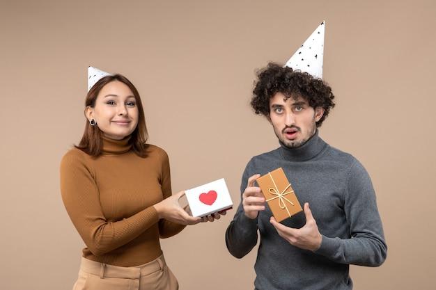 Neujahrsschießen mit emotionalem lustigem jungem paar tragen neujahrshutmädchen mit herz und kerl mit geschenk auf grau