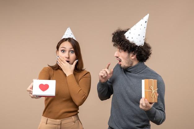 Neujahrsschießen mit emotionalem verrücktem schockiertem jungem paar tragen neujahrshutmädchen mit herz