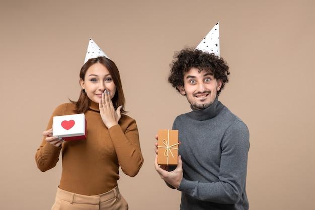 Neujahrsschießen mit glücklichem jungem paar tragen neujahrshutmädchen mit herz und kerl mit geschenk auf grau