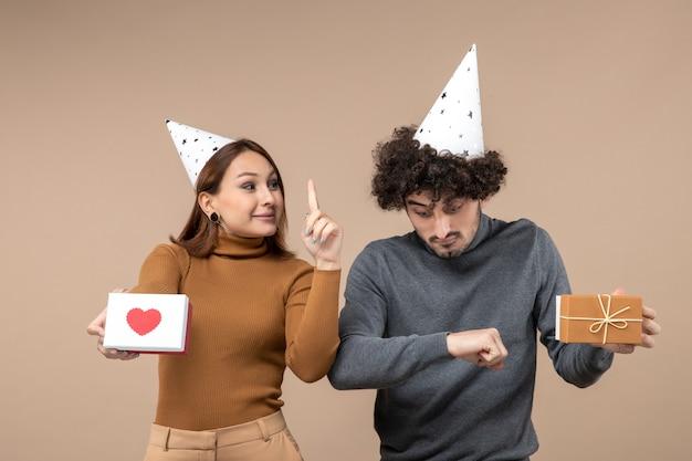 Neujahrsschießen mit jungem paar tragen neujahrshut glückliches mädchen mit heraufweisendem herzen und kerl