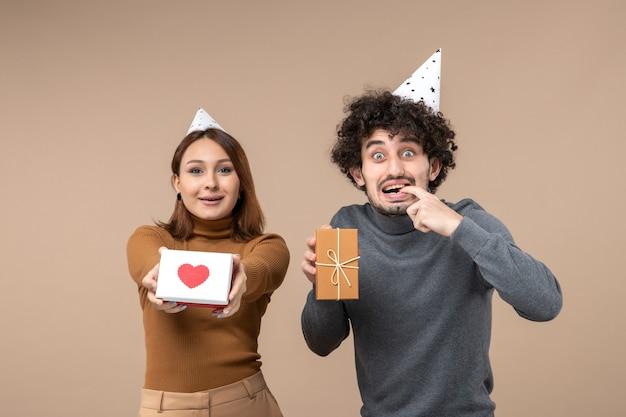 Neujahrsschießen mit jungem paar tragen neujahrshut glückliches mädchen mit herz und überraschtem kerl mit geschenk auf grau