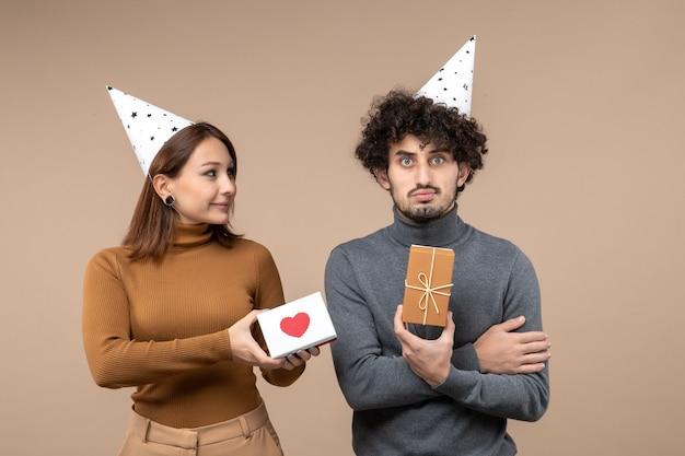 Neujahrsschießen mit jungem paar tragen neujahrshut romantisches mädchen mit herz und traurigem kerl mit geschenk auf grau