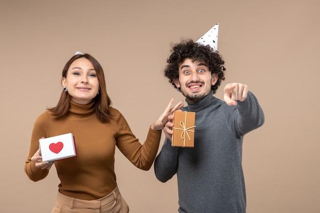 Neujahrsschießen mit lustigem jungem paar tragen neujahrshutmädchen mit herz und kerl mit geschenk auf grau