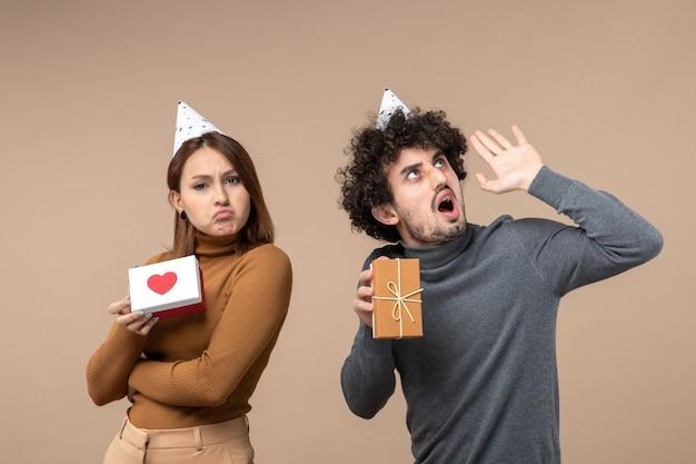 Neujahrsschießen mit nervösem jungem paar tragen neujahrshutmädchen mit herz und kerl mit geschenk auf grau