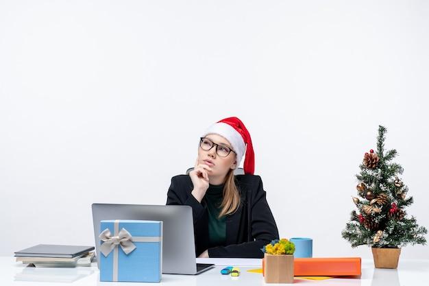 Neujahrsstimmung mit attraktiver frau mit einem weihnachtsmannhut, der nachdenklich an einem tisch mit einem weihnachtsbaum und einem geschenk darauf im büro sitzt