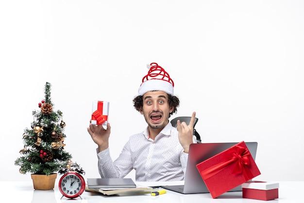 Neujahrsstimmung mit aufgeregtem emotionalem jungem geschäftsmann mit weihnachtsmannhut, der im büro sitzt und sein geschenk hält, das für kamera auf weißem hintergrund aufwirft