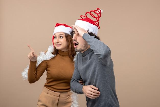 Neujahrsstimmung mit aufgeregten kühlen zufriedenen reizenden reizenden reizenden paaren, die rote weihnachtsmannhüte genießen, die zusammen auf grau sind