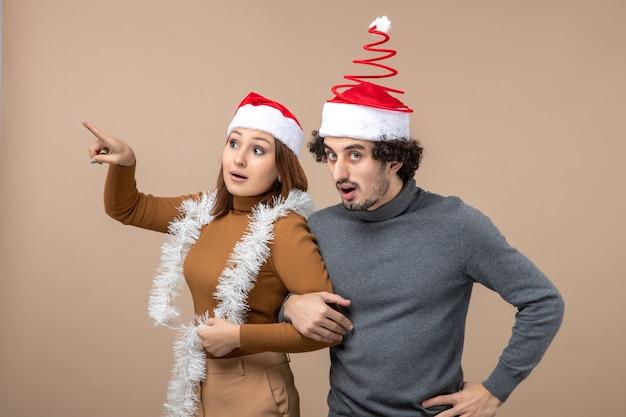 Neujahrsstimmung mit aufgeregten kühlen zufriedenen reizenden reizenden reizenden paaren, die rote weihnachtsmannhüte genießen