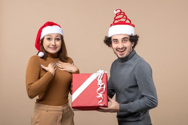 Neujahrsstimmung mit dem lustigen glücklichen reizenden paar, das rote weihnachtsmannhüte auf grau trägt