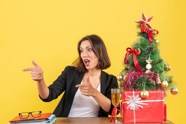 Neujahrsstimmung mit der schönen geschäftsdame, die etwas zeigt und an einem tisch im büro sitzt