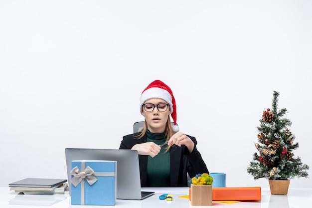 Neujahrsstimmung mit ernsthafter blonder frau mit einem weihnachtsmannhut, der an einem tisch mit einem weihnachtsbaum und einem geschenk auf ihm auf weißem hintergrund sitzt