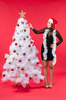 Neujahrsstimmung mit glücklichem schönem mädchen in einem schwarzen kleid mit weihnachtsmannhut, der weihnachtsbaum auf rot verziert