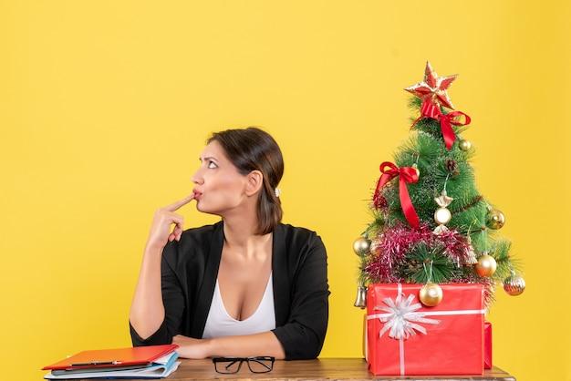 Neujahrsstimmung mit glücklicher junger frau im anzug mit geschmücktem weihnachtsbaum im büro auf gelb