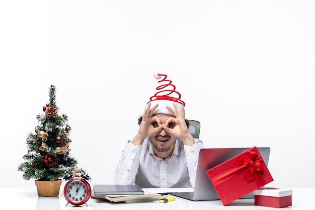 Neujahrsstimmung mit jungem geschäftsmann mit weihnachtsmannhut, der brillengeste im büro auf weißem hintergrund macht