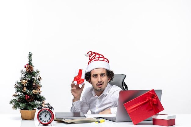 Neujahrsstimmung mit jungem geschäftsmann mit weihnachtsmannhut, der im büro sitzt und sein geschenk hält, das für kamera auf weißem hintergrund aufwirft