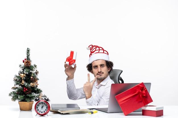 Neujahrsstimmung mit jungem geschäftsmann mit weihnachtsmannhut, der im büro sitzt und sein geschenk hält, das zwei auf weißem hintergrund zeigt