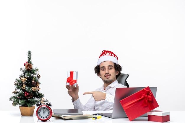 Neujahrsstimmung mit jungem geschäftsmann mit weihnachtsmannhut, der im büro sitzt und sein geschenk zeigt, das für kamera auf weißem hintergrund aufwirft