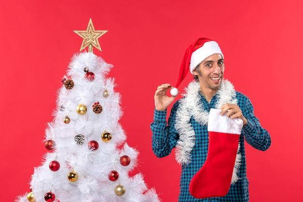Neujahrsstimmung mit jungem mann mit weihnachtsmannhut, der weihnachtssocke und -dekoration hält