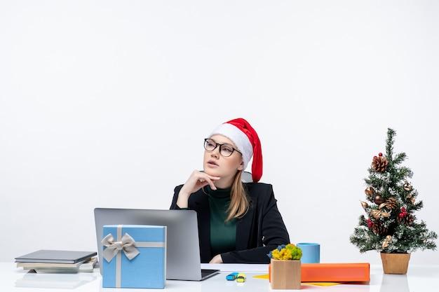 Neujahrsstimmung mit junger verwirrter attraktiver frau mit einem weihnachtsmannhut, der an einem tisch mit einem weihnachtsbaum und einem geschenk darauf im büro sitzt