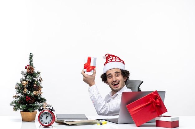 Neujahrsstimmung mit lächelndem positivem jungen geschäftsmann mit weihnachtsmannhut, der im büro sitzt und ein geschenk auf weißem hintergrund hält