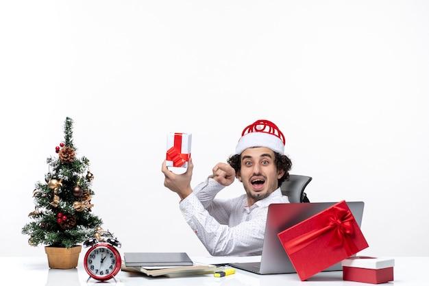 Neujahrsstimmung mit lächelndem positivem jungen geschäftsmann mit weihnachtsmannhut, der im büro sitzt und sein geschenk auf weißem hintergrund zeigt
