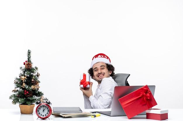 Neujahrsstimmung mit lächelndem positivem jungen geschäftsmann mit weihnachtsmannhut, der im büro sitzt und sein geschenk glücklich auf weißem hintergrund zeigt