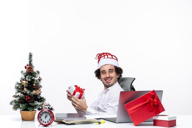Neujahrsstimmung mit lächelndem positivem lustigem jungem geschäftsmann mit weihnachtsmannhut, der im büro sitzt und sein geschenk auf weißem hintergrund zeigt