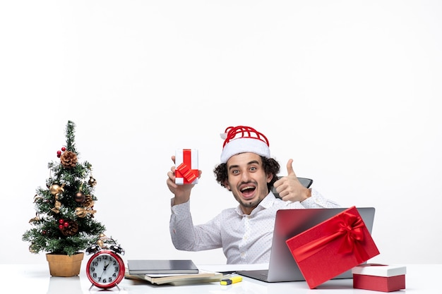 Neujahrsstimmung mit lächelndem zufriedenem jungen geschäftsmann mit weihnachtsmannhut, der im büro sitzt und sein geschenk auf weißem hintergrund hält