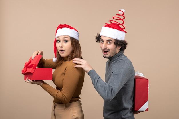 Neujahrsstimmung mit lustigem reizendem paar, das rote weihnachtsmannhüte auf grau trägt
