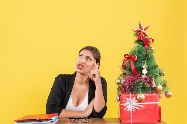 Neujahrsstimmung mit nervöser junger frau im anzug mit geschmücktem weihnachtsbaum im büro auf gelb