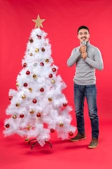 Neujahrsstimmung mit positivem kerl gekleidet in jeans, die nahe geschmücktem weihnachtsbaum stehen