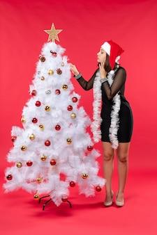 Neujahrsstimmung mit schönem mädchen in einem schwarzen kleid mit weihnachtsmannhut, der weihnachtsbaum auf rotem filmmaterial verziert
