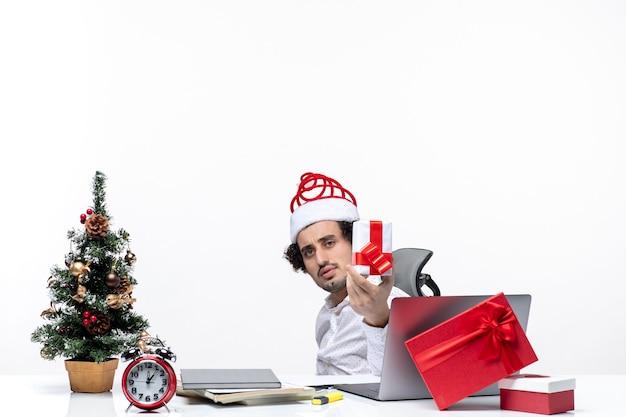 Neujahrsstimmung mit traurigem unzufriedenem jungen geschäftsmann mit weihnachtsmannhut, der im büro sitzt und sein geschenk auf weißem hintergrund erhöht