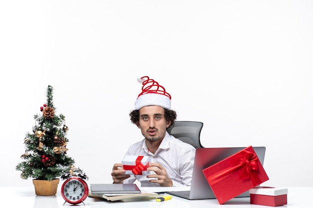 Neujahrsstimmung mit traurigem unzufriedenem jungen geschäftsmann mit weihnachtsmannhut, der im büro sitzt und sein geschenk auf weißem hintergrund hält