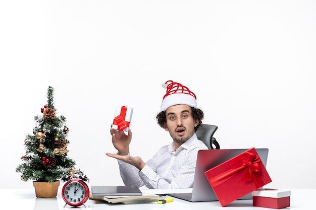 Neujahrsstimmung mit überraschtem jungen geschäftsmann mit weihnachtsmannhut, der im büro sitzt und sein geschenk hält, das für kamera auf weißem hintergrund aufwirft